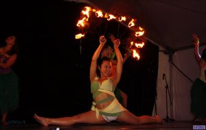 A performer doing the splits onstage holding lit fire fans